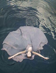 Woman wearing gown in water