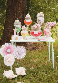 Cute vintage pinwheels and candy table. Was able to copy the pinwheels in this photo by folding scrapbook paper (see the pinned tutorial), gluing it onto a paper doily, and using a cute round sticker or paper for the middle. Could attach a bamboo skewer and stick in a jar of candy or hang from the ceiling from fishing line or beading line.