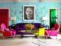 Colorful living space with traditional armchairs upholstered in bright magenta, and a purple sofa