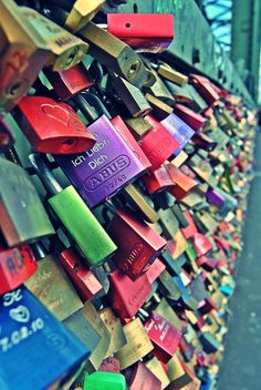 Love locks ~in  Paris.  Twisting Colorful padlocks hanging on bridge from the colorful mountains.
