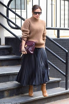 Stylish: The singer-turned-designer was effortlessly chic in her casual ensemble, teaming a chunky beige knit with a pleated maxiskirt