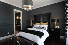 Atmosphere Interior Design    charcoal gray black yellow sophisticated masculine bedroom design with gray walls, tall black leather tufted wingback bed headboard, yellow velvet pillows, white & black fabric drapes and bolster pillows, black leather modern ottomans, glossy black mirrored nightstands and silvery gray drum pendant.