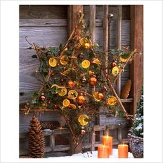 Star made from sticks decorated with Hedera, Vaccinium, dried orange slices and Christmas tree decorations hanging on wall