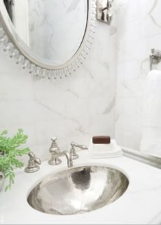 The custom vanity topped with calacatta marble in the powder room is a standout and surrounds a gorgeous nickel undermounted sink and faucet from Waterworks. The fabulous mirror is by Baker. By Parlor Design.