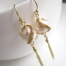"""Creamy orbs of freshwater pearls have been wrapped into swirls of 14k gold-fill wire.  Tassels of gold-fill chain hang from the bottom of the pearls and ear hooks make for a total length of 2.5"""". Simp"""