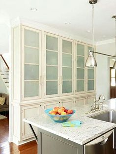 Light & Livable: Storage  Located directly across from the central island, a wall of 12-inch-deep floor-to-ceiling cabinets function as pantry space. Frosted-glass panels break up the solid wall of cabinetry and add to the kitchen's light and airy feel while keeping clutter out of sight.