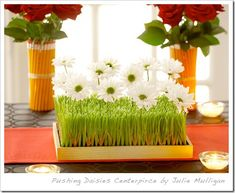 Use wheatgrass. You can cut it to fit any tray or vase that you want to use, and insert purple flowers that are placed in floral tubes.