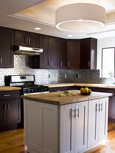 Team Jonathan installed butcher-block countertops, a new stove, fixtures and a Brazilian cherry floor in this Brother Vs. Brother kitchen renovation. A stainless steel backsplash creates a modern, easy-to-clean surface.