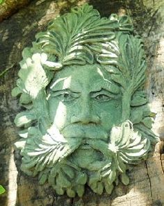 """The Calm Greenman Sculpted by noted artist Richard Warsin of Design Toscano fame. This piece was inspired by a green man from a cathedral in Scotland. Hand cast in cement and hand finished with an eco based cement stain ( What Else) he is what we need in our stressed filled lives! Get him Today! 1.5 lbs. 7 & 1/2"""" H x 5 & 1/2"""" W Made in USA"""
