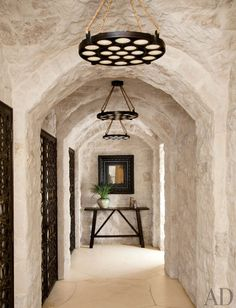 Atelier AM created a trio of bronze pendant lights inset with translucent sand dollars for a hallway in Laguna Beach, California.