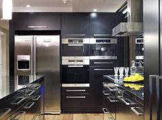 The highly reflective surfaces in this apartment kitchen include Nero Marquina solid marble countertops and black lacquered cabinets. Three pendant lights above the island help to visually soften the all-black material palette.