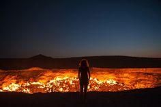 """03-Door-to-Hell A Cratera de Darvasa, também chamada de Porta para o Inferno é um campo de gás natural localizado em Derweze (também escrito Darvaza, que significa """"porta""""), na província de Ahal, no Turcomenistão. A cratera é conhecida pela sua chama que vem queimando continuamente desde 1971, alimentada pelos ricos depósitos de gás natural na área. Ela exala um forte cheiro de enxofre que pode ser sentido à distância.  Veja mais aqui…"""