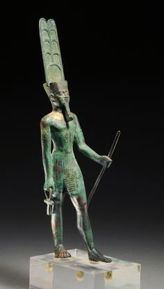 EGYPTIAN BRONZE STATUETTE OF AMUN    Striding, holding ankh and staff (both added later), wearing a headdress surmounted by twin plumes and a solar disk; wide gold-inlaid pectoral collar.  Superb!    XXVIth Dynasty, 664-525 BC