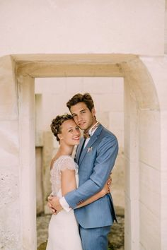 Bride wearing lace wedding dress and braided, Groom wearing light blue linen suit
