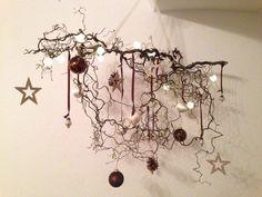 Korkenzieherhaselnuss behängt mit batteriebetriebener Lichterkette und div. weihnachtlichen Accessoires.