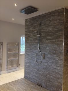 Imola Colosseum staggered mosaic tiles create an architectural backdrop to the Aqualisa Ilux shower system. The wefloor was a bespoke size made by On The Level and the wall drain is by Geberit. No more standing on the waste!