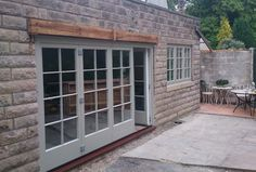 Timber light grey folding doors with georgian bars http://www.oraclewindowsolutions.com/timber-doors/bifold-doors