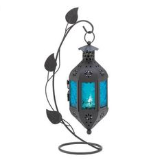 "**NEW PAGAN HOME DECOR @ Eclectic Artisans** At the end of a graceful vine hangs a lantern of purest blue, blazing with color from a petite candle tucked inside. This freestanding lamp makes a stunning appearance no matter where you choose to enjoy it! Weight: 0.8 lbs. Metal, Glass.    3 3/4"" x 6 1/2"" x 12 1/4"" high"