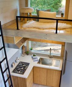 Inside the Live/Work Tiny Home is a home office, bedroom loft, storage loft, and an L-shaped kitchen with 3-burner cooktop and full size refrigerator.