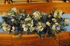 Arranjo floral em mesa de convidados de casamento em casa em clima vintage romântico com a cor do ano da pantone para 2016: serenity blue. Para o arranjo foram usadas garrafinhas, flores brancas e nude, folhas de eucalipto e pinhas nas cores escolhidas pela noiva.