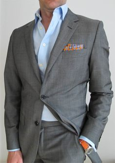 gray suit, blue shirt, orange watch