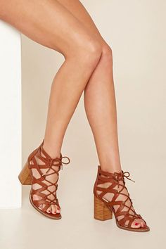 A pair of faux leather heels featuring cutout detailing, an exposed back zipper, a lace-up top, and a chunky block heel.