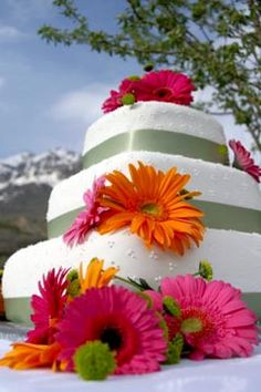 Three tier pink and orange gerbera daisies on a square white wedding cake