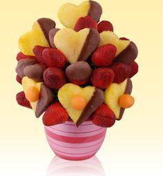 Arreglo de frutas con chocolate...fresas naturales, corazones de piña con demi cubierta de chocolate amargo y perlas de melón.