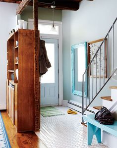 """8 Inspiring No Coat Closet Entryways // Live Simply by Annie: """"8. Finally, in what is perhaps the cleverest solution of the bunch in my opinion–I give you the free-standing entryway storage unit (via Style At Home). 1. It divides the room, distinguishing the entry from the living room. 2. It features living room-y things on that side (read: TV), while across the wood divide there are hooks and cubbies for coats and co. Now that's smart thinking. """""""