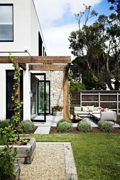 """The charming garden evokes villas in Italy. Key plants include French lavender, red geraniums and ornamental grapevine (*Vitis Vinifera*), which has beautiful burgundy foliage in autumn. Gloster Designs Cloud **sofa**, [Cosh Living](http://coshliving.com.au/?utm_campaign=supplier/