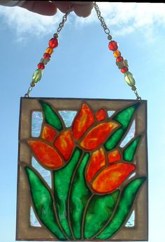 Orange Red Tulips Stained Glass Art Gifts, Wall Décor, Flower Floral Art Panel, Suncatcher, Wall Hanging, Ornament. This fiery orange and red tulips stained glass panel has been painted by me with semi transparent glass stains on textured art glass. (Pic#1) shows it adorned with red, green and orange crystal and glass beads and tiny gold plated butterflies with a gold finished chain. Although I don't have pictures yet, it can be made with red, pink or yellow flowers (actually you can specify…