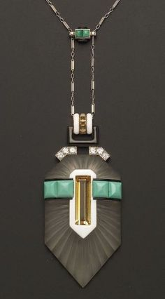 Art Deco Platinum, Rock Crystal and Gem-set Pendant Necklace, the fluted crystal plaque set with step-cut citrines, pyramidal cabochon turquoise, and full-cut diamond melee, black and white en plein enamel accents, suspended from a delicate baton link chain with conforming slide, pendant 2 3/4 x 1 1/4 in., lg. 18 1/2 in., French assay and hallmarks, possibly Pickmann, Paris.  Estimate $2,000-3,000  Sold for $17,625