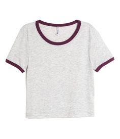 Top corto en punto suave con ribete en color de contraste en cuello y mangas.