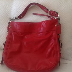 SALECoach Red Patent Handbag Great looking purse with silver hardware/side buckles and tan interior. Two large interior zip pockets and three slide pockets. It has two slight pen marks in back of purse which are slightly noticeable (pic 4)priced accordingly. The inside is clean with the exception of slight marks of lipstick inside of one of the large zip pockets. Coach Bags