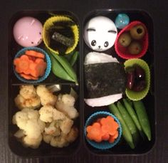 My first bento - smoked salmon onigiri, olives, carrot flowers, sugar snaps. steamed spicy cauliflower, sunomono (panda cup), and ginger (pig cup)