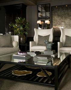 Beautiful sophisticated living space. Note the two toned sofa and mirrors flanking major art on either side. Also enjoy the non traditional seating arrangement