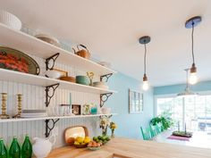 A pair of Edison bulbs are strung on basic pendant wiring for simple industrial lighting fixtures that don't obscure the view from the kitchen into the dining space. Open shelving, light blue walls and butcher block countertops combine to create a cottage look.