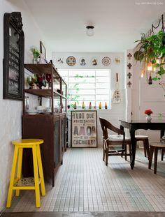 Cozinha integrada com móveis rústicos, plantas e objetos reaproveitados que ganharam nova função.