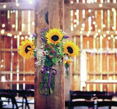 rustic wedding idea: hang arrangements on barn beams as farm wedding decor.