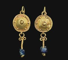 A PAIR OF ROMAN GOLD AND GLASS EARRINGS   CIRCA 2ND-3RD CENTURY A.D.   Each with a shield framed by twisted wire, plain wire and beaded wire, with six granules around the perimeter, centered by a large granule, a granule above, joined to the long earwire, hooked below into a loop on, each suspending a loop above volutes and a length of twisted wire threaded through a blue glass bead