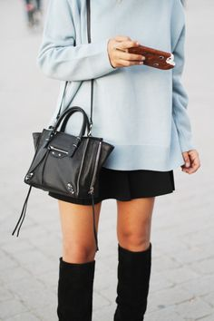 Aida Domenech is wearing a pale blue vintage sweater, black skirt and boots from Zara, bag from Balenciaga