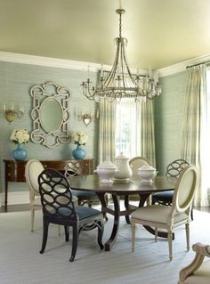 For a more subtle look, a luxurious grass-cloth wall covering in soft green. Grass-cloth can add texture and interest to any space but I try not to use it in high traffic areas. This dining room has several wow factors; the chandelier, the painted ceiling & the mirror.