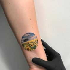 Sunflower field circle tattoo on the left inner forearm.