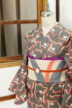 チャコールグレーの地に、薔薇の花のようにも見えるアールデコテイストの装飾パターンが描かれたウール紬の単着物です。