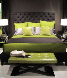 Upholstered gray bed styled with greens and stainless accent tables.