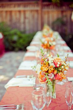 Tangerine textured tablecloth and floral arrangements for this table setting. JH
