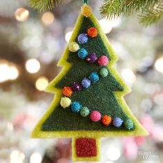 This sweet tree is an adorable Christmas ornament craft the kids can make. Cut a tree shape from light green wool. Cut out a dark green tree accent and a brown trunk accent and sew these pieces onto light green layer. Use needle and thread to sew on purchased beaded felt balls in a zigzag pattern. Stitch a yarn loop at the top for hanging. /