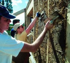 Plastering is done directly onto the straw packed into the walls between load-bearing frames does't need added netting to provide grip for finishes, by apprentices who will carry this technique out into the community.