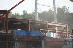 Steel construction continues near the base of a light tower.