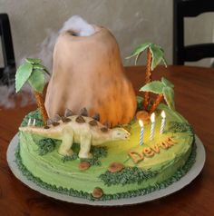 Boy Birthday Dinosaur volcano cake - I made this for my sons third birthday party. Fondant covered chocolate cake volcano, fondant dinosaur painted with petal dust, fondant palm leaves mounted on pretzel sticks. I added dry ice in water for the smoke effect- a big hit with the kids!